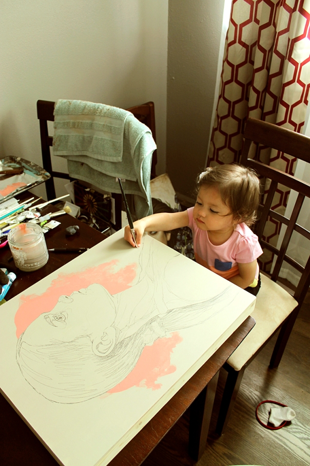 My daughter pretending to paint with the final drawing.